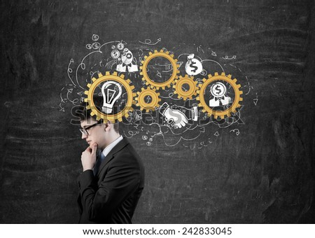 businessman thinking with gold gears on head
