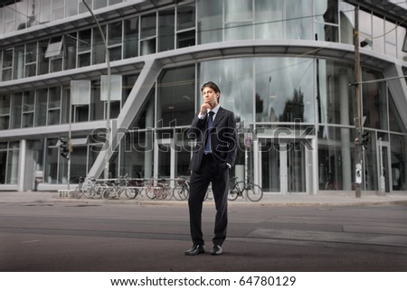 Businessman thinking with office building on the background - stock photo