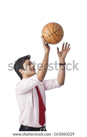 Businessman throwing a basketball - stock photo