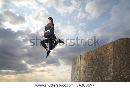 Businessman throwing himself from a rock into the void - stock photo