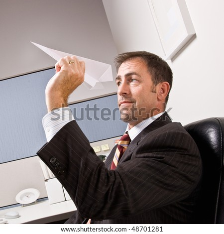 Businessman throwing paper airplane - stock photo