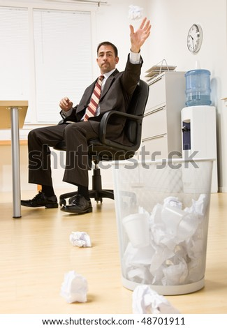 Businessman throwing paper in trash basket - stock photo