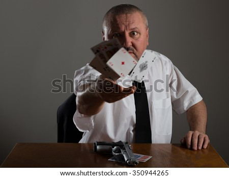 Businessman throwing playing cards at the table
