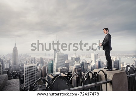 Businessman throwing some banknotes from a skyscraper - stock photo