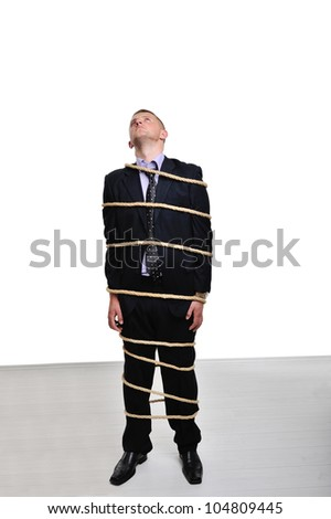 Businessman tied up with a rope looking up - stock photo