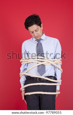 Businessman tied up with a rope struggle to get free - stock photo