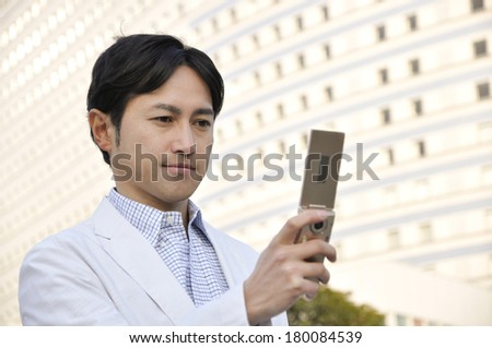 Businessman to check the mail of mobile phone - stock photo