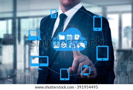 Businessman touching a cloud connected to many objects on a virtual screen, concept about internet of things. - stock photo