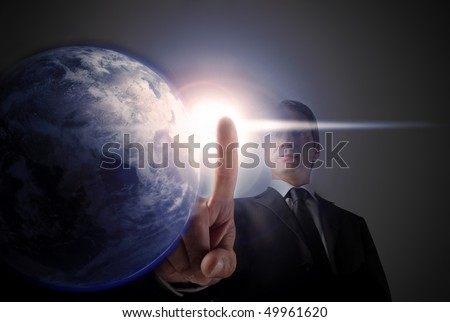 Businessman touching a light next to the earth - stock photo