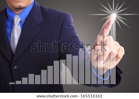 Businessman touching growing graph in studio - stock photo