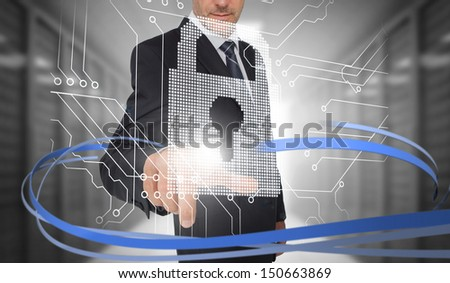 Businessman touching lock on futuristic interface with swirling lines in data center - stock photo