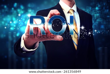 Businessman touching ROI (return on investment) on blue technology background - stock photo