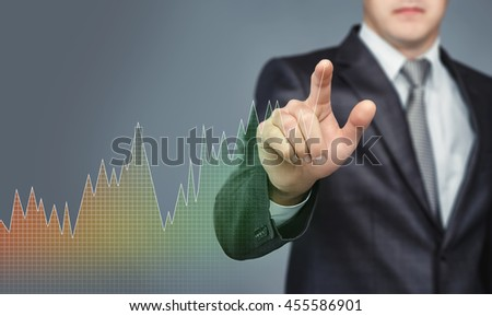 Businessman touching the digital touchscreen with diagram with his finger. Innovative technology. Business presentation. Rise of shares. Succesful management. - stock photo