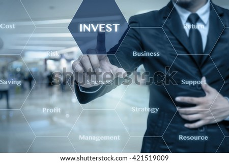 Businessman touching the Invest icon with business success virtual screen on the Abstract blurred photo of store in department store bokeh background, Business technology concept  - stock photo