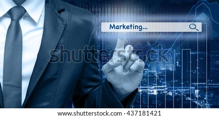 """Businessman touching the virtual searching bar with """"Marketing"""" on the trading graph over the cityscape blurred background, Internet concept,Elements of this image furnished by NASA - stock photo"""
