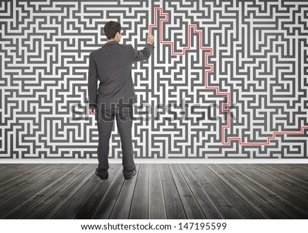 Businessman tracing a red line on a maze drew on the wall - stock photo