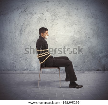 Businessman trapped in a chair with rope