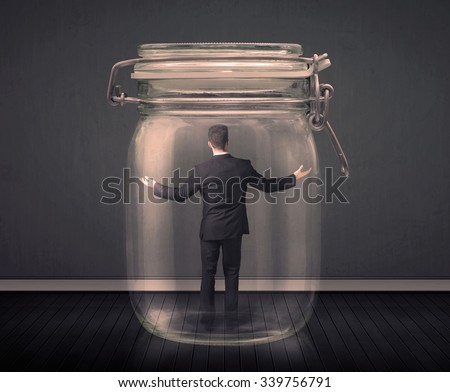 Businessman trapped into a glass jar concept on background - stock photo
