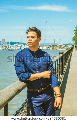 Businessman traveling in New York. Wearing blue collarless shirt, holding sunglasses, a young guy standing by harbor in Hudson River, waiting for you. Boats, bridge on background. Instagram effect.