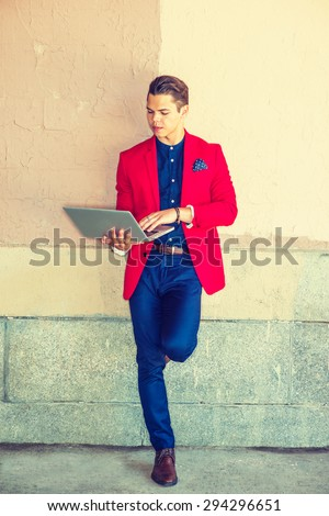 Businessman traveling, working in New York. Dressing in red blazer, blue collarless shirt, pants, leather shoes, a guy standing against wall on street, reading, working on laptop computer. Man Fashion - stock photo