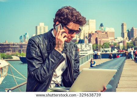 Businessman traveling, working in New York. Wearing sunglasses, a young guy with beard, sitting on bench at harbor, working on laptop computer, talking on phone in the same time. Instagram effect.  - stock photo