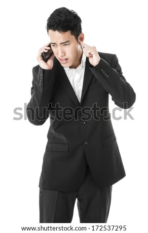 Businessman trying to hear whats on the phone - stock photo