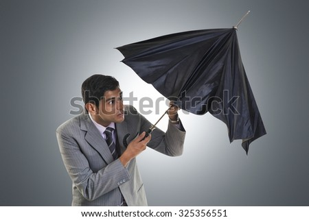 Businessman trying to open umbrella