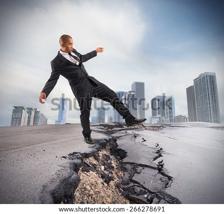 Businessman trying to overcome a crisis break - stock photo
