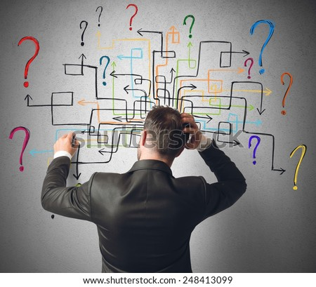 Businessman trying to solve a maze questions - stock photo