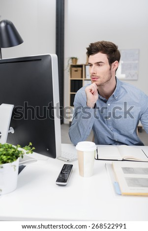 Businessman trying to solve a problem sitting at his desk staring at his computer screen with narrowed eyes and a thoughtful expression - stock photo