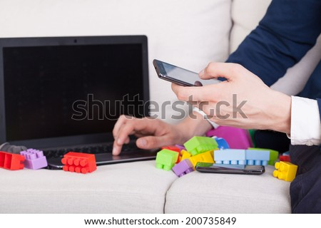 Businessman trying to work at home and take care of child - stock photo
