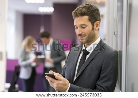 Businessman typing a message on mobile phone in modern office - stock photo