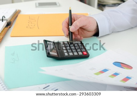 Businessman typing on a calculator, at the office - stock photo