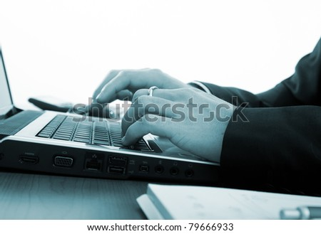 Businessman typing on a laptop - blue toned image