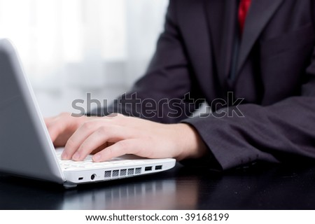Businessman typing on a notebook (shallow DOF, hand in focus) - stock photo