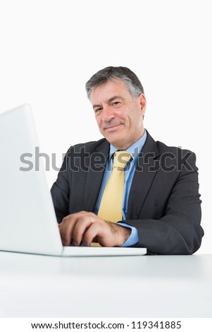 Businessman typing on laptop at his desk