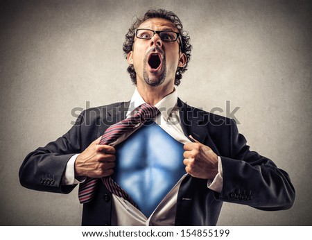 businessman unbuttons his suit and becomes superman - stock photo