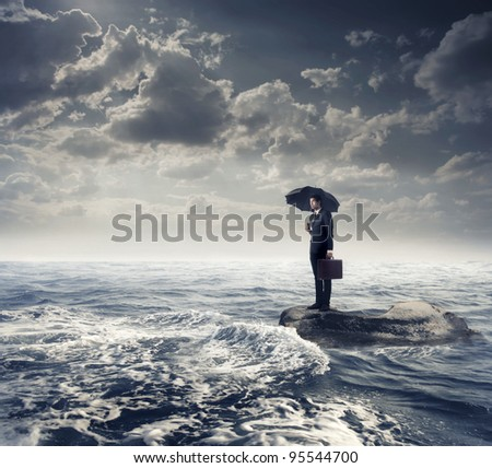 Businessman under an umbrella standing on a rock in the middle of a slight sea - stock photo