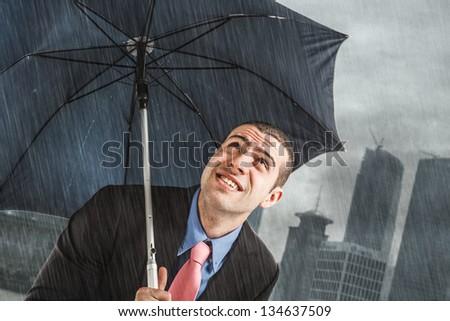 Businessman under heavy rain - stock photo