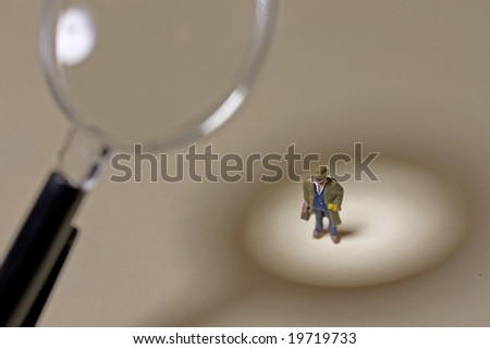 Businessman under magnifying glass - stock photo