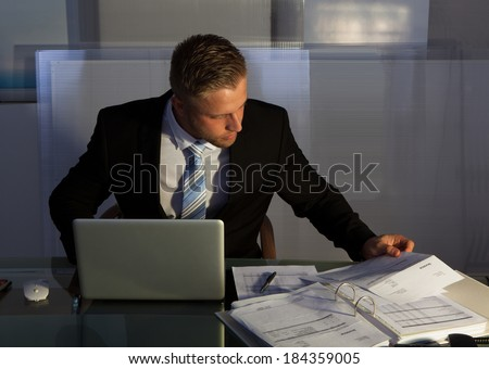 Businessman under pressure working overtime late into the evening sitting at his desk collating a report for a deadline in the morning - stock photo