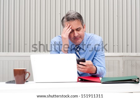 Businessman under stress, fatigue and headache at office - stock photo