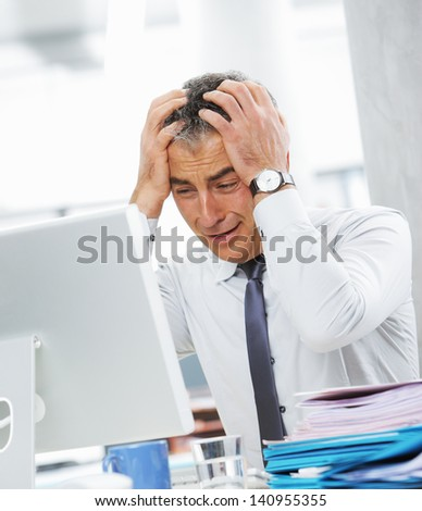 Businessman under stress, fatigue and headache, he kept his hands behind his head - stock photo
