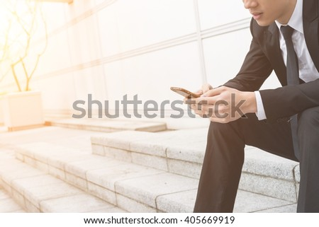 Businessman use of mobile phone and sitting outside - stock photo