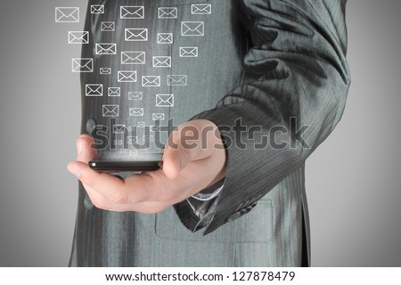 Businessman uses smart phone with virtual envelopes - stock photo
