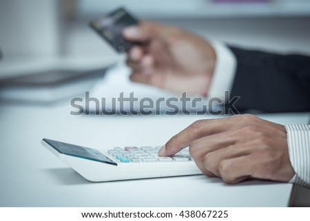 Businessman using a calculator to calculate his payment on credit card in vintage color filter - stock photo