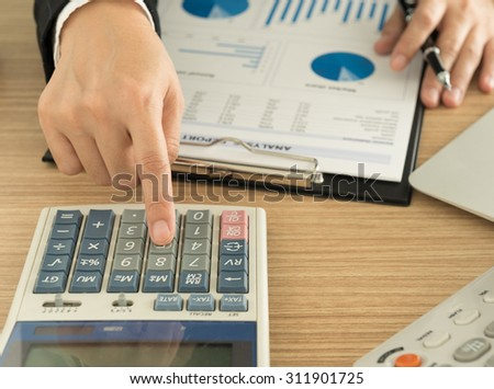 Businessman using a calculator to calculate the numbers and he working at office. - stock photo