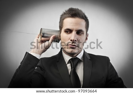 Businessman using a can and a rope as a telephone - stock photo