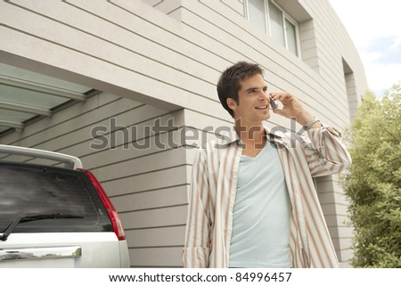Businessman using a cell phone at home, standing by his car. - stock photo