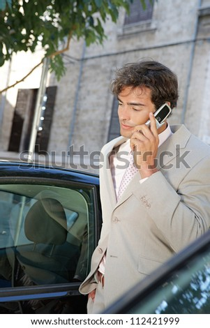 Businessman using a cell phone to make a phone call while standing by some cars in the city.